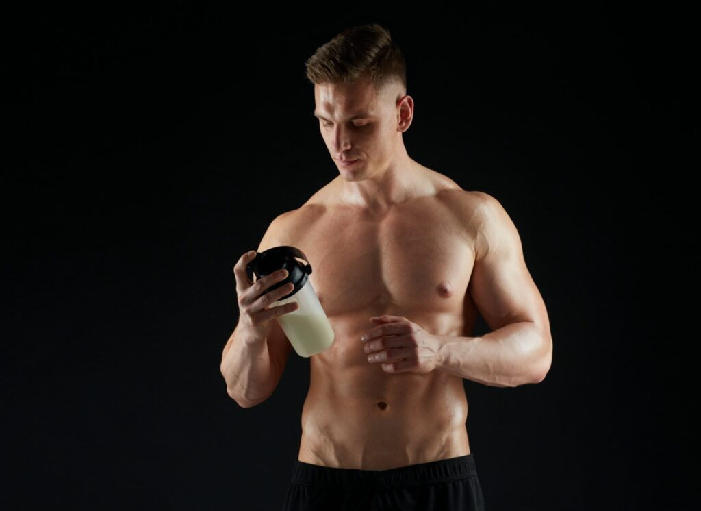 sport, bodybuilding, fitness and people concept - young man or bodybuilder with protein shake bottle and bare torso over black background athleticfesttival.pl